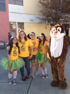 Make-Shift Cheerleaders -- From left, seniors Thao Duong, Barbara Rojas, Jazmin Gomez and Karla Aragon created their own green and gold tutus to boost spirit at the Homecoming Rally Nov. 6. They are not cheerleaders but do support the teams at Fremont. Marquis Wilhite (at right) has been the main cheerleader for the sports teams in the last two years with his Tiger mascot costume.