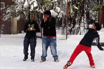 At right, Angel Manzo, a junior in Architecture Academy, throws a snowball as Media Academy junior Jerome Pope (left) and Architecture Academy junior Kamossi Brooks (middle) look on at Camp Sylvester near Pinecrest on Dec. 11. The overnight was the first to be organized for two of Fremont's three academies.