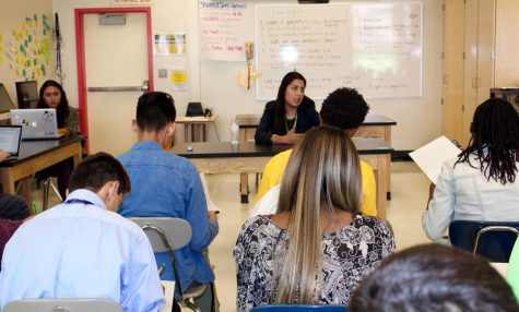 Students take notes at a press conference with Fremont's assistant principal, Nidya Baez, FHS '03 (center).