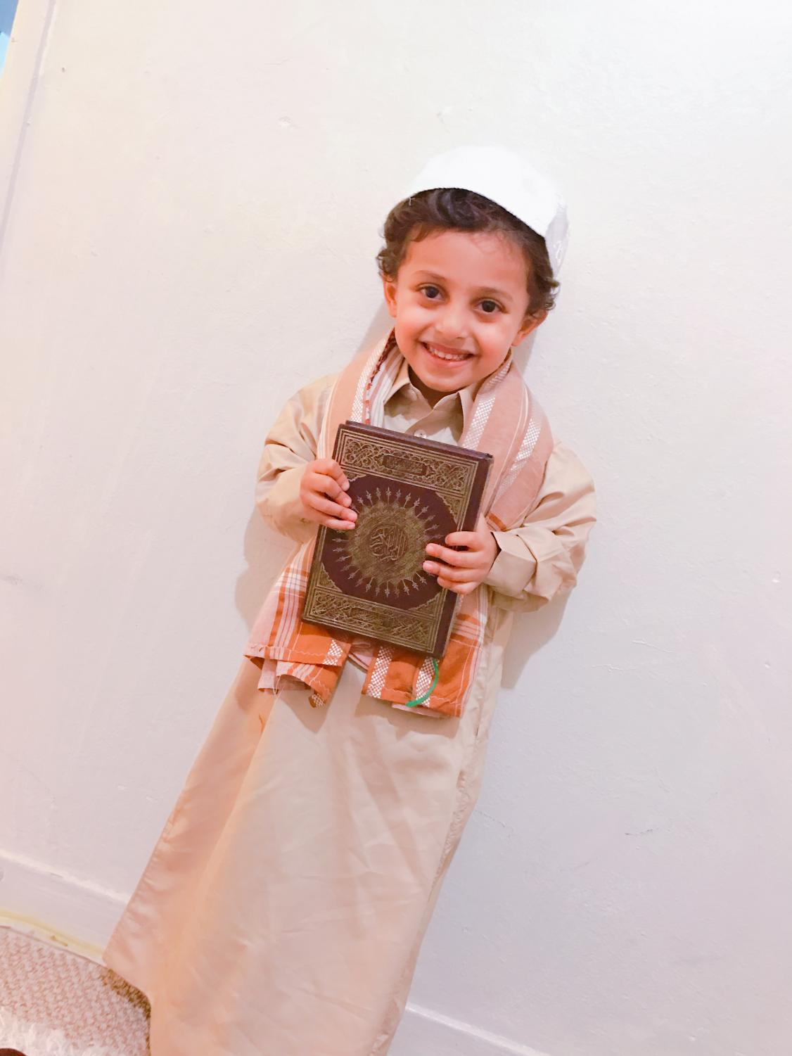 Boy wearing a Thwab and holding a Quran